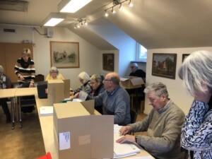 Medlemmarna klistrar etiketter till Årsbokens kuvert